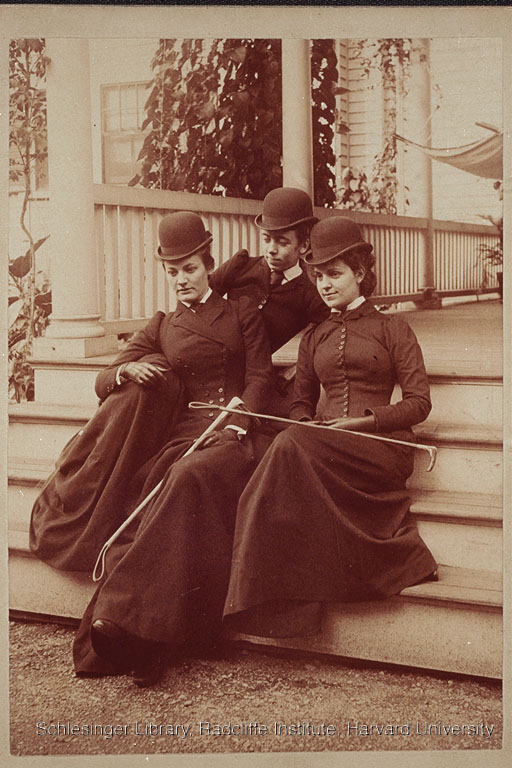 Group portrait of three Berkeley Street School students seated on porch steps. All are wearing riding habit, with two of the women holding crops.