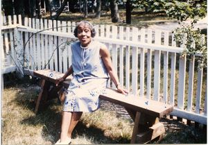 Portrait of Dorothy West seated outdoors on a bench