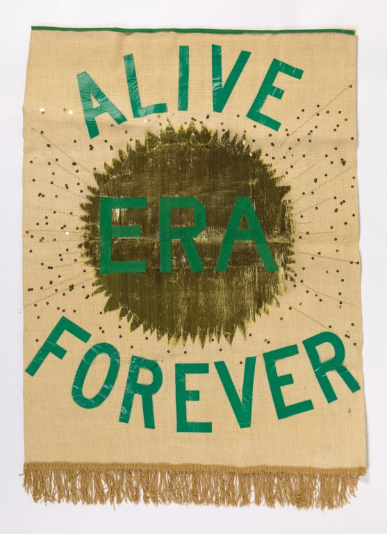 "Burlap banner with ""ERA Alive Forever"" in green tape, stitched on over gold sun and gold sequins. Gold fringe along bottom of banner."