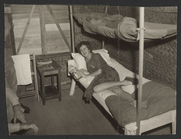 Julia Child lounging on her cot in the OSS headquarters, reading an issue of Health & Efficiency