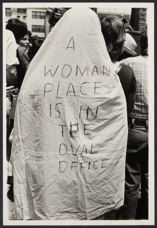 "A sheet saying ""A woman's place is in the oval office"""