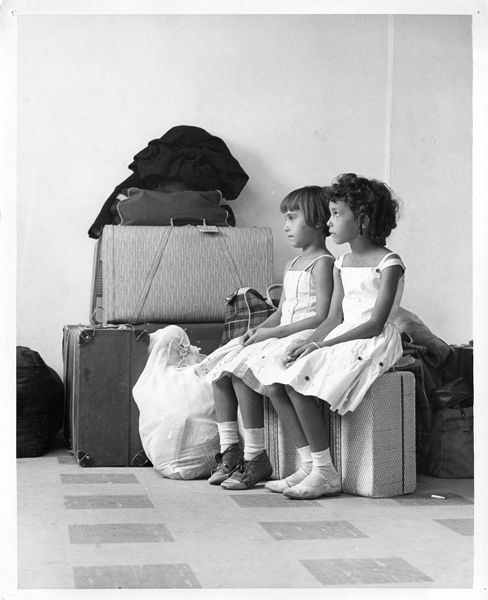Two young girls seated on a suitcase wait for processing at the Cuban Refugee Center