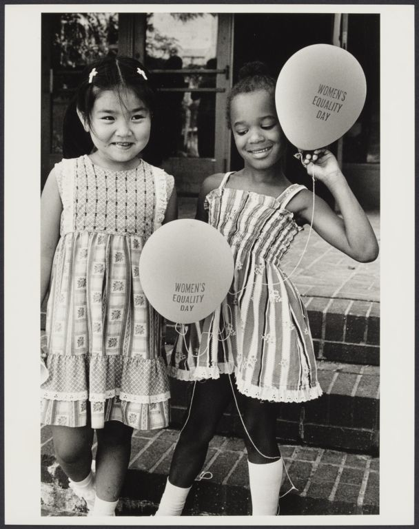 """Two young girls holding """"Women's Equality Day"""" balloons, 1980"""