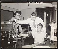 [Nate Davis, Eugene M. Landis, Marvin Sleisenger (seated), and Robert Hopkins recording data in physiology lab], Digital Object