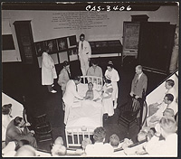 [Dr. Greene Fitzhugh (hands on chair) watching as patient is examined during lecture demonstration at MGH], Digital Object