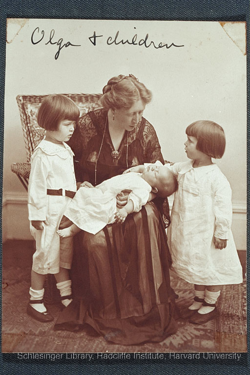 """""""Olga"""" seated with an infant on her lap. Woman is leaning forward to show two girls (presumably her daughters) the baby. The child on the right rests her hand on the infant's chest."""