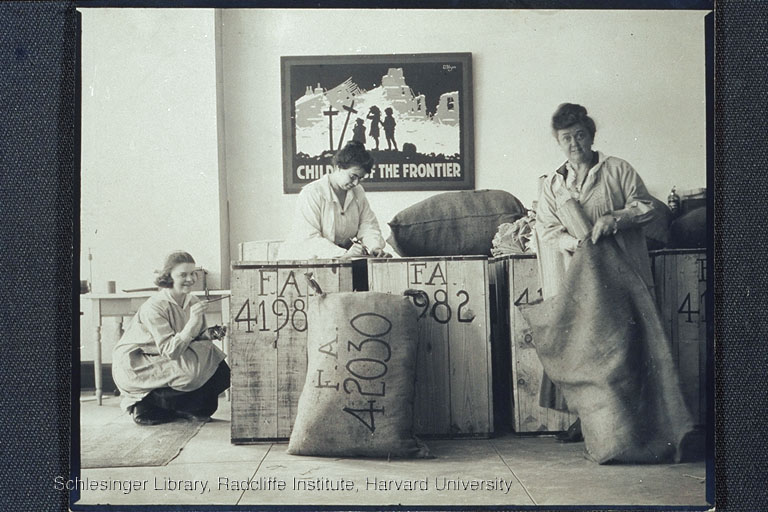 """Three unidentified women packaging supplies indoors: one labels boxes (right); one writes (center); and one puts something into a bag. A poster for the """"Children of the Frontier"""" hangs on the wall behind them."""