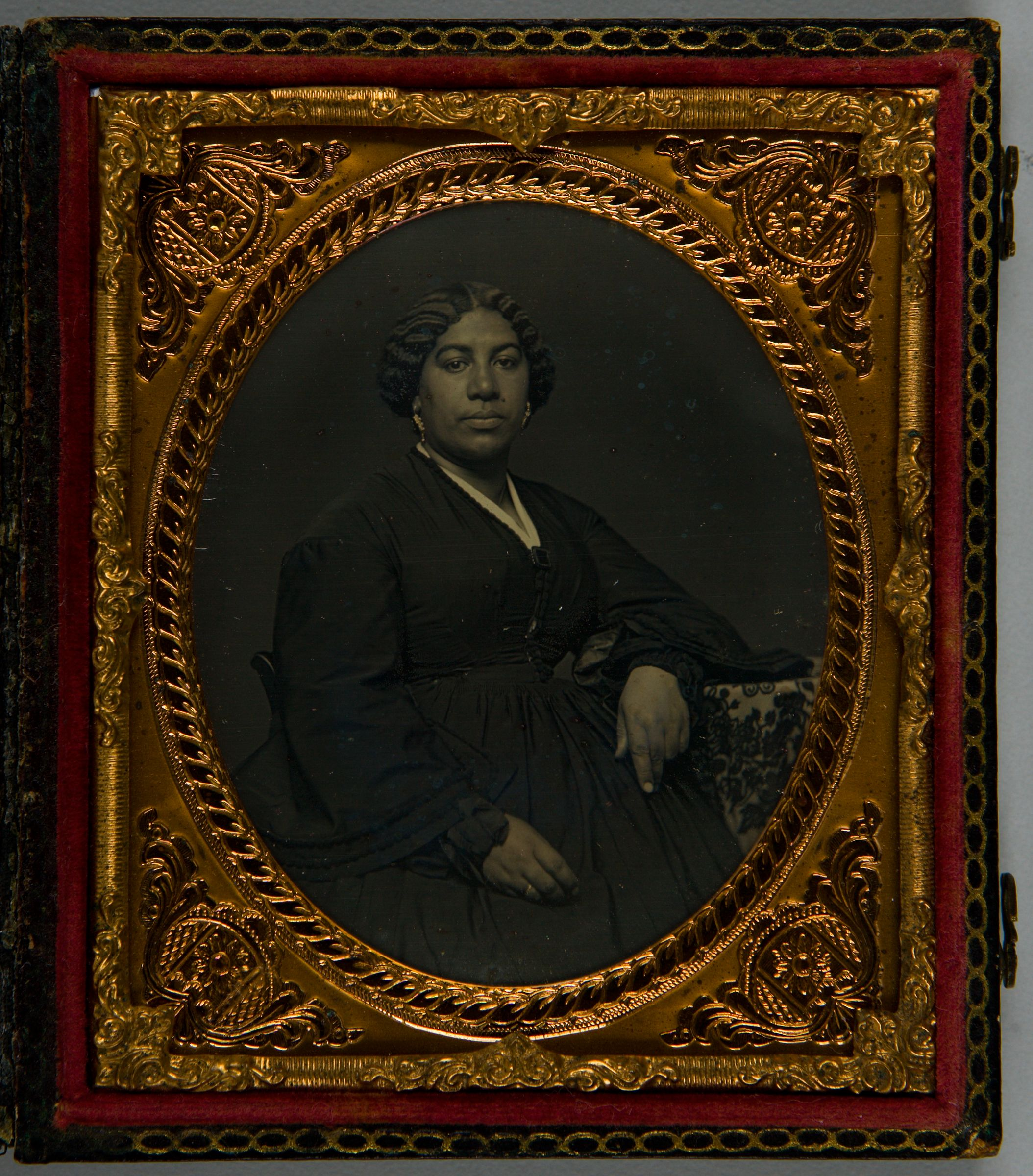 Untitled (Half Length Portrait Of African American Woman, Seated And Leaning Against Tapestry-Covered Table)