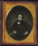 Man, arm resting by daguerreotype case