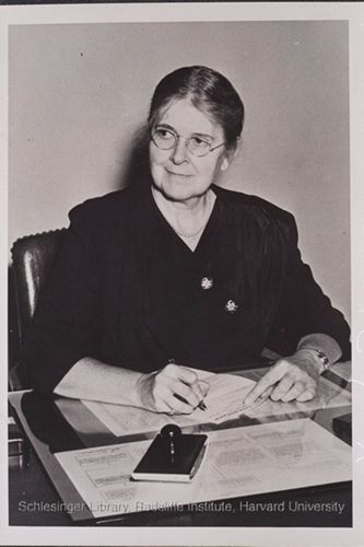 Martha May Eliot seated at her desk