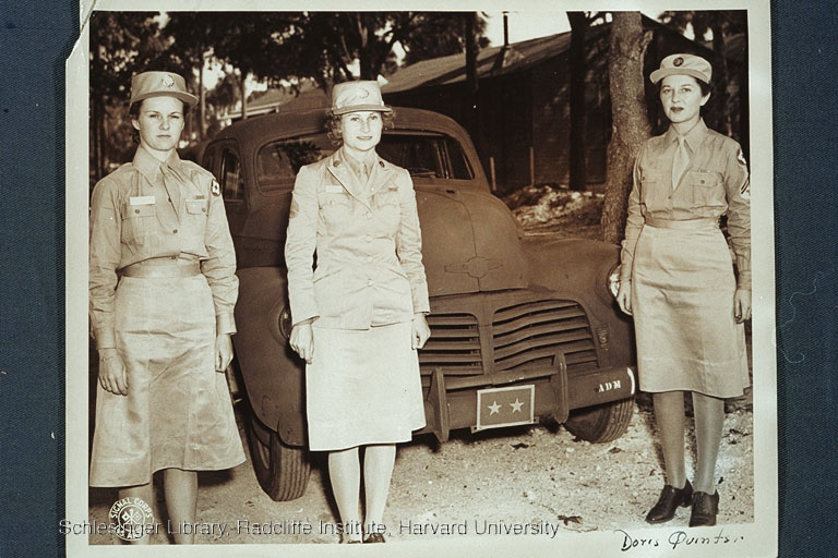 Three members of the WAAC or WAC standing in front of a military automobile, possibly during World War II. The woman on the right is probably Doris Quinten.