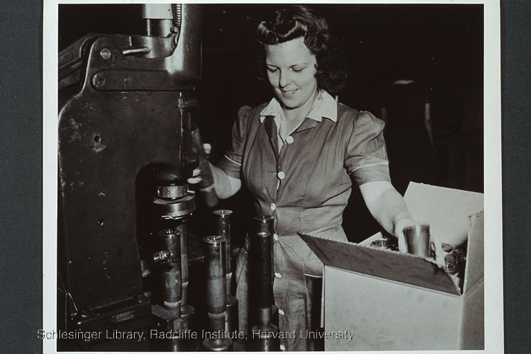 Unidentified munitions worker box operating a shell-related machine and boxing finished shells.