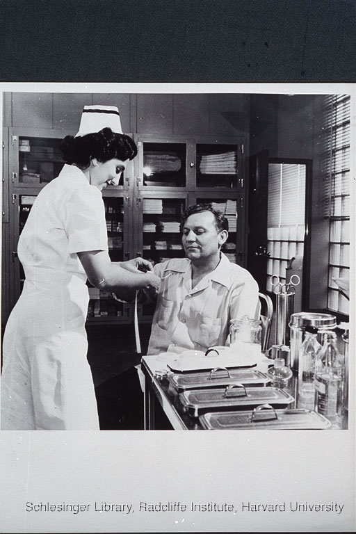 Unidentified nurse bandaging a man's finger inside a medical office. Behind them are cabinets stocked with first aid supplies; next to them on a table are stainless steel instruments and storage boxes.