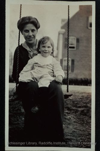 Anna Blackwell (Belden) seated outdoors on a swing with her son Lawrence Putnam Belden on her lap.
