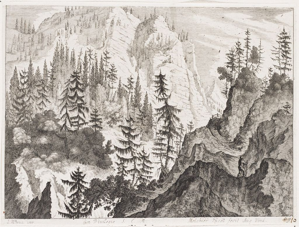 Mountains Spotted With Pine Trees And Man With Walking Stick Ascending A Path