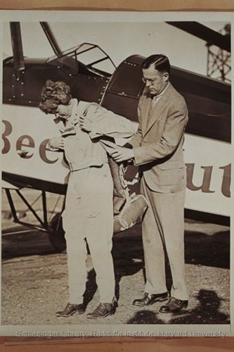 Amelia Earhart strapping on a parachute with the assistance of her husband, George Palmer Putnam. Earhart is preparing to pilot a cross-country flight in a Beech-Nut autogiro as part of a feasibility test. Earhart and Putnam are standing in front of the aircraft.