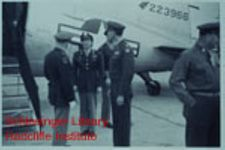 U.S. Army soldiers and civilians standing in front of an airplane outdoors during Catherine Shouse