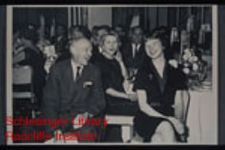 Karen Peterson Wilken attending a dinner with unidentified men and women.  She is seated on the right.