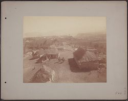 [View of village with thatched roof buildings and men on horseback]