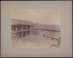 [View of men in courtyard of building under construction]