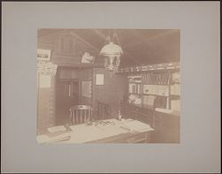 [View of office showing desk, overhead lamp, photos on wall, bookshelves]