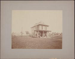 [View of house with men and women seated on porch]