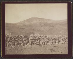 [View of stone wall with mountains in background]