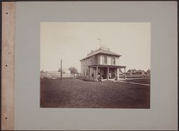 [View of house with men and women seated on porch, may be the home of Prof. Loud in Colorado, photograph]
