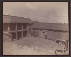 [View of men in courtyard of building]