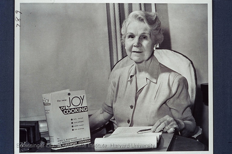 Irma Rombauer seated at a table holding a copy of her cookbook, The Joy of Cooking.