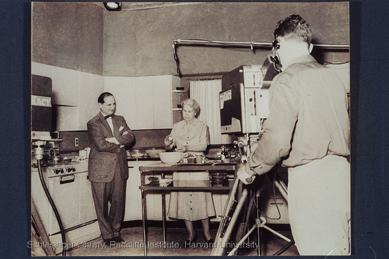 Irma Rombauer performing a cooking demonstration on television while an unidentified man looks on