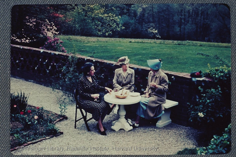 Corinna Lindon Smith (center) lunching with Mrs. Jasper Whiting (left) and Mrs. Ralph Bradley (right) seated at a small garden table. Women's Travel Club Picnic.