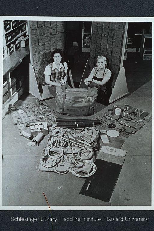 """Group portrait of two women factory workers, Betty Miller and Juanita Cole, seated indoors on the factory floor of Consolidated Vultee Aircraft Corporation's Convair Coronado Feeder workshop. In front of them is a completely assembled """"Liberator"""" maintenance kit and a display of allthe items that go into the kit."""