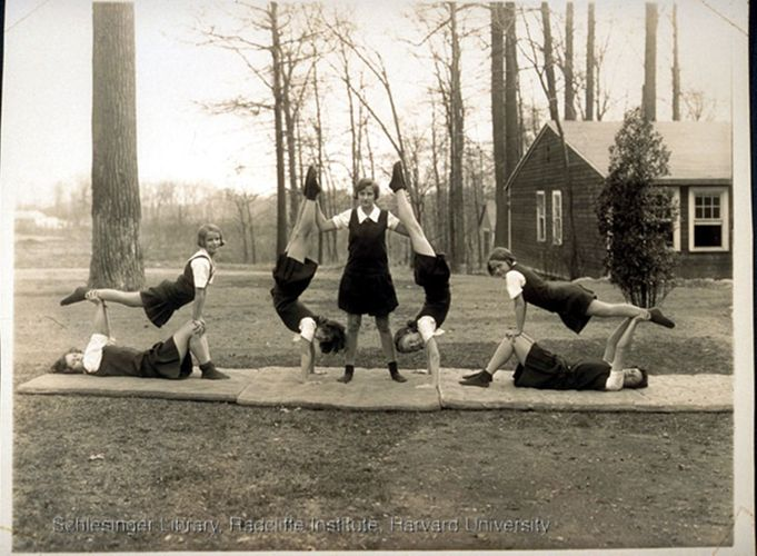 Women students at the Roger Ascham School posing in gymnastic or cheering formations, outdoors, on mats.