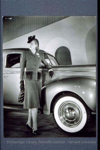 Model dressed in a suit and posed next to a Ford sedan ca. 1938-1945.  Harold Haliday Costain (n.d.), photographer, Free-Lance Photographer's Guild (n.d.), photographer.