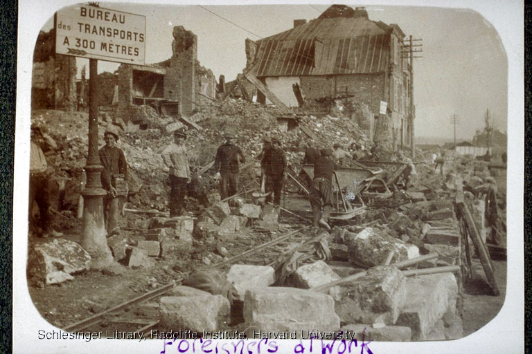 Men working to clear away the ruins of buildings in the village of Pérrone