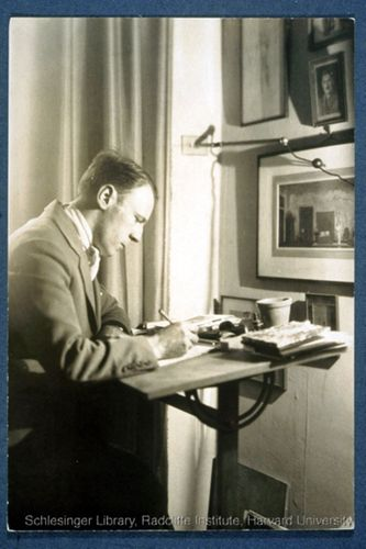Informal portrait of Roland Young seated indoors at his desk, writing. Framed works hang on the wall in front of him.