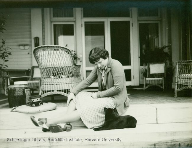 Katharine Lane Weems sitting on a porch with a dog