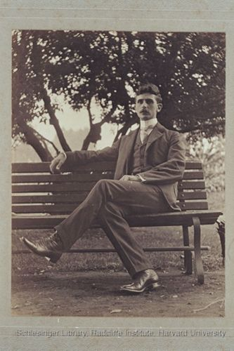 Unidentified man sitting outdoors on a bench.