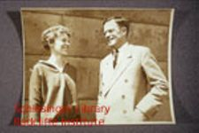 Earhart and Putnam standing together.  In one, they are looking at a paper, possibly a chart.