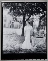Untitled (young woman in long white dress standing by well topped with potted plants)