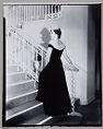 Untitled (Woman In Black Dress With Decorative White Collar Seen From Back At Base Of Staircase)