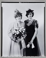Untitled (two women in flowered hats, one holding large bouquet)