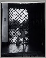 Untitled (little girl standing in front of metal gated doorway, looking back over shoulder, stuffed animal to side)