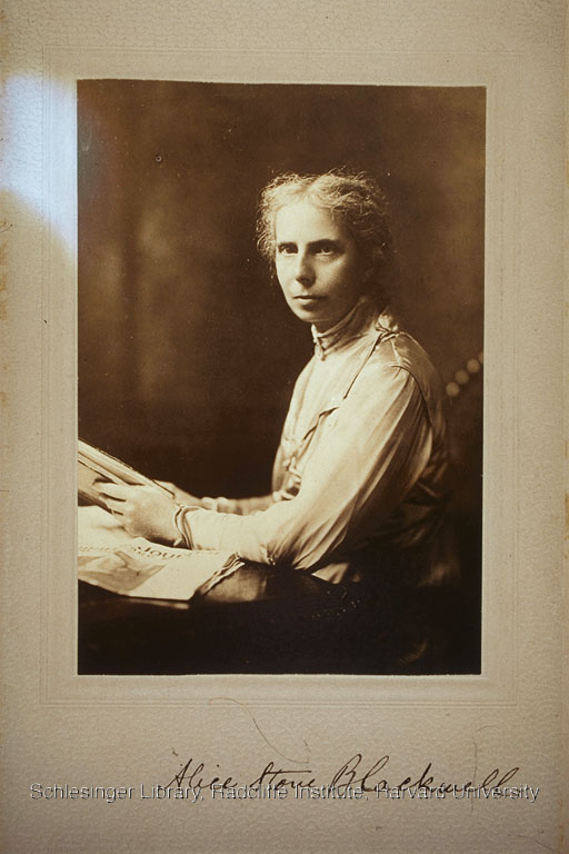 Alice Stone Blackwell seated at a table with book in her hands and an edition of Woman's Journal beside her.