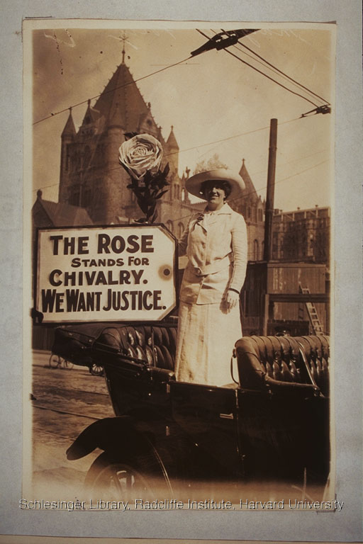 """Woman with a sign reading """"The Rose Stands For Chivalry. We Want Justice."""" Trinity Church, Boston, 1914."""