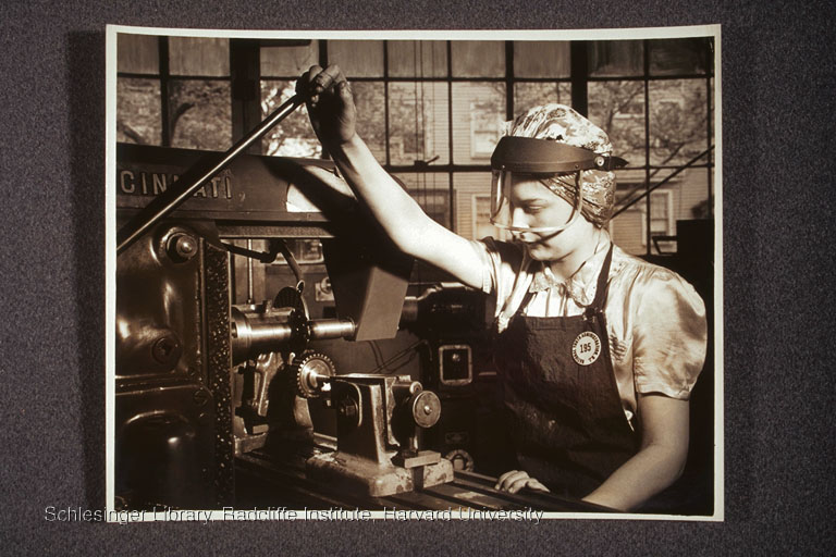 Unidentified woman, working at a machine in a factory.