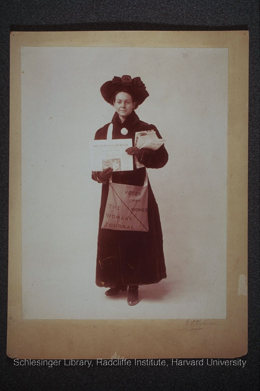 Florence Luscomb dressed in a winter coat and hat, selling The Woman's Journal.