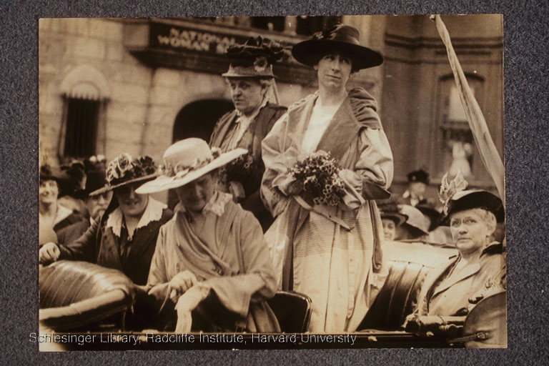 Carrie Chapman Catt (standing, left) and Jeannette Rankin (standing, right) in automobile with three other women on the occasion of Rankin's arrival in Washington, D.C. as the first U.S. Congresswoman, April 1917.