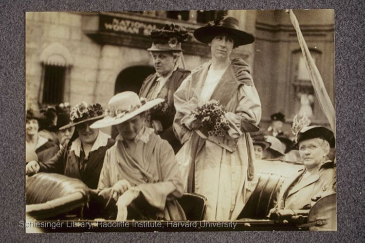 Carrie Chapman Catt (standing, left) and Jeannette Rankin (standing, right) in automobile with three other women, in front of the National American Woman Suffrage Association headquarters on the occasion of Rankin's arrival in Washington, D.C. as the first U.S. Congresswoman.